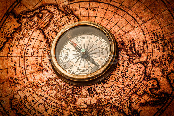 Vintage compass lies on an ancient world map. Stock photo © cookelma