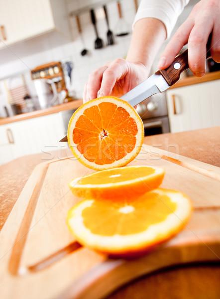 Stock photo: Woman's hands cutting orange