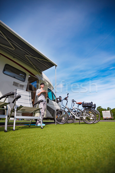 Woman is standing with a mug of coffee near the camper. Stock photo © cookelma