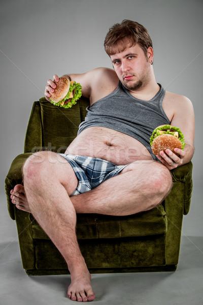 Uomo grasso mangiare hamburger poltrona alimentare Foto d'archivio © cookelma