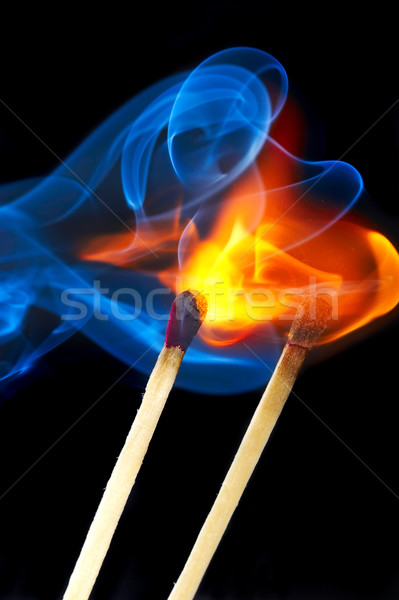Photo of a burning match in a smoke on a black background Stock photo © cookelma