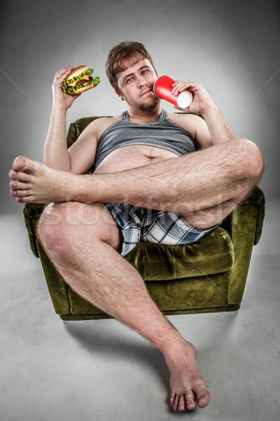 Vet man eten hamburger fauteuil stijl Stockfoto © cookelma