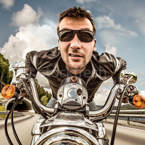 Stock photo: Funny Biker in sunglasses and leather jacket racing on mountain