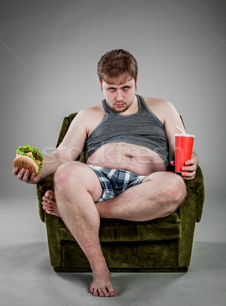 Gros homme manger hamburger assis fauteuil alimentaire Photo stock © cookelma