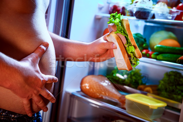 Hungry man holding a sandwich in his hands and standing next to  Stock photo © cookelma