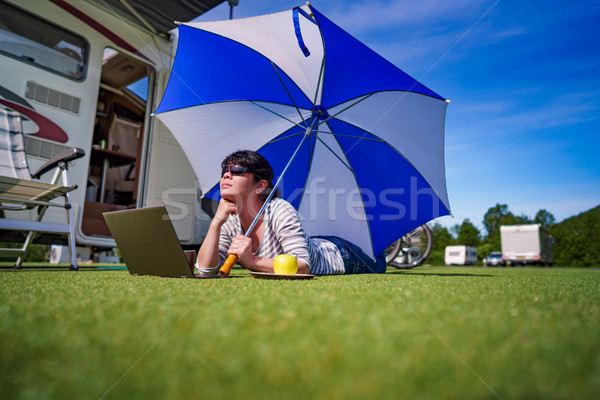 Woman on the grass, looking at the laptop under umbrella near th Stock photo © cookelma