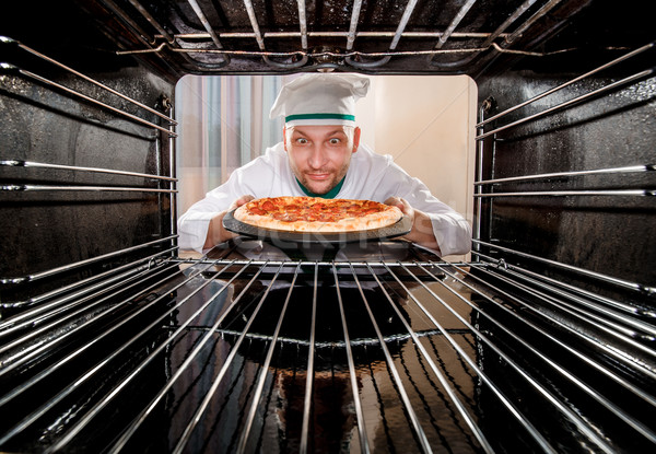 Chef cooking pizza in the oven. Stock photo © cookelma