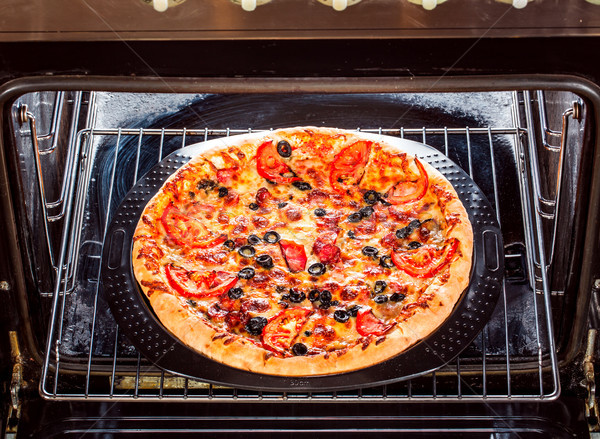 Appetizing pizza in the oven. Stock photo © cookelma