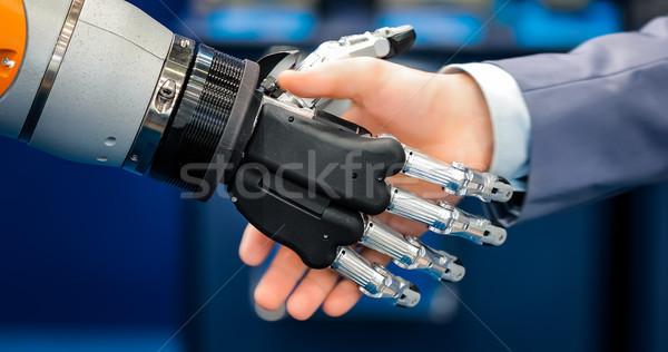 Hand of a businessman shaking hands with a droid robot. The conc Stock photo © cookelma