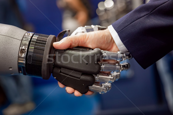 Hand of a businessman shaking hands with a Android robot. Stock photo © cookelma