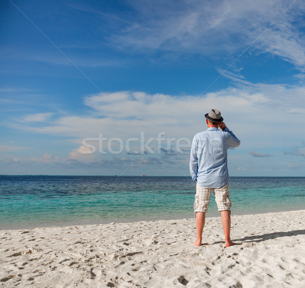 Man walking along a tropical beach in the Maldives. Stock photo © cookelma