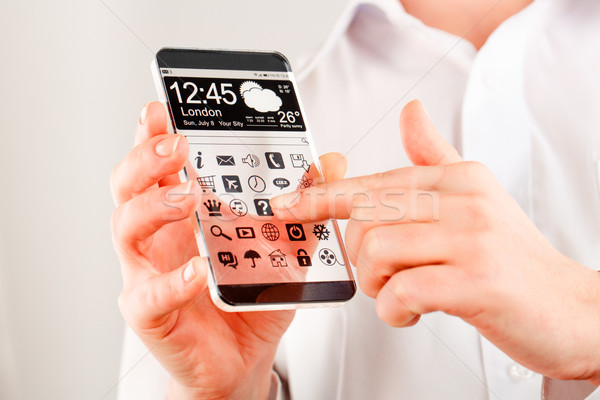 Smartphone with transparent screen in human hands. Stock photo © cookelma