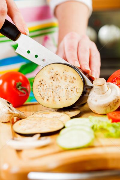 Woman's hands cutting aubergine eggplant Stock photo © cookelma