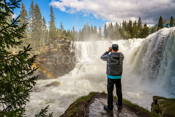 Nature photographer tourist with camera shoots while standing Ri Stock photo © cookelma