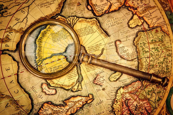 Vintage magnifying glass lies on the ancient map of the North Po Stock photo © cookelma