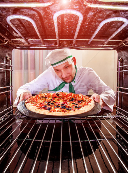 Stock photo: Chef cooking pizza in the oven.