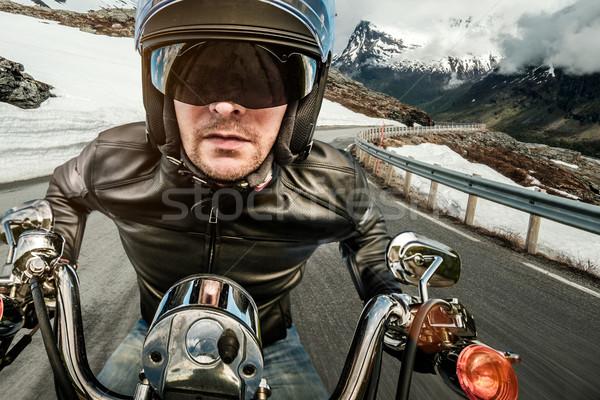 Biker in helmet and leather jacket racing on mountain serpentine Stock photo © cookelma