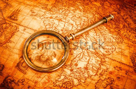 Vintage compass and goose quill pen lying on an old map. Stock photo © cookelma