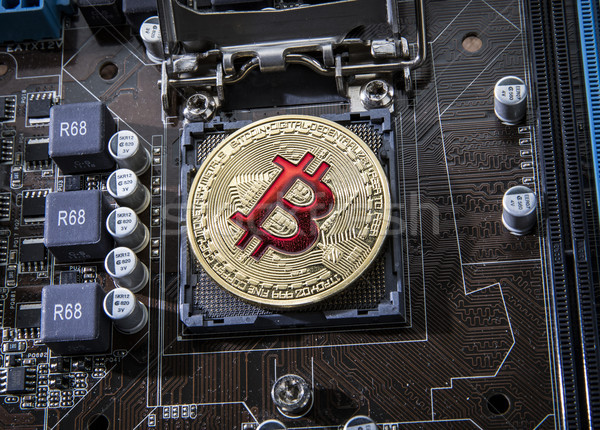 Gold Bit Coin BTC coins on the motherboard. Bitcoin is a worldwi Stock photo © cookelma