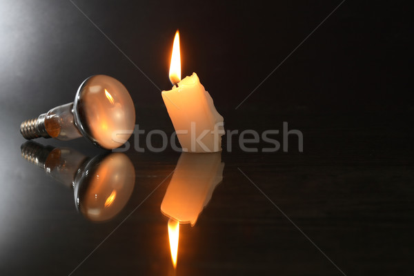 Electric Bulb Against Candle Stock photo © cosma