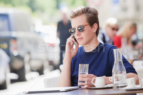 Young Man Sitting in Outside Coffeehouse Talking on Phone Stock photo © courtyardpix