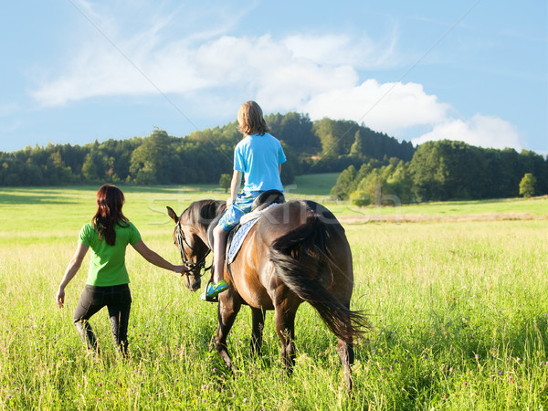 Horseback Riding Lessons - Woman Leading a Horse with a Boy in S Stock photo © courtyardpix