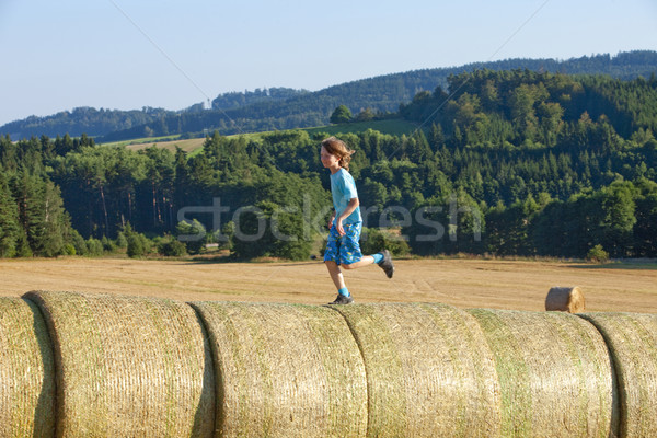 Boy Running on Bales of Hay  Stock photo © courtyardpix
