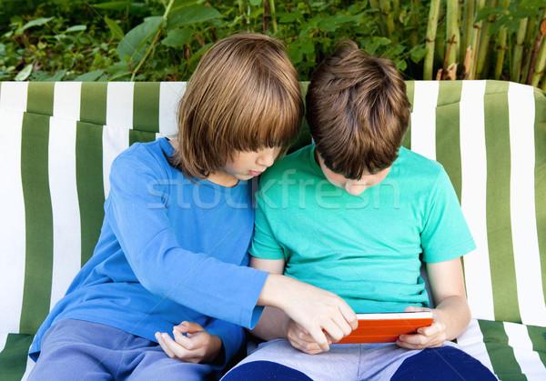 Dwa chłopców posiedzenia ogród gry tabletka Zdjęcia stock © courtyardpix