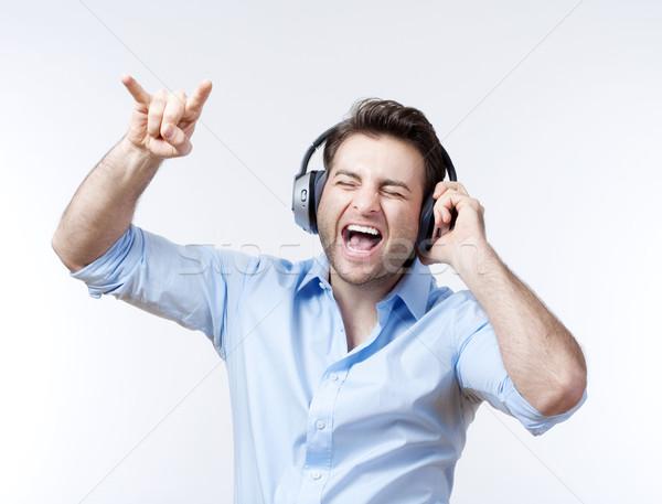 Man Blauw shirt luisteren naar muziek geïsoleerd Stockfoto © courtyardpix