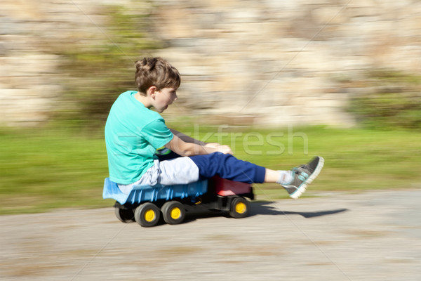 Boy Riding Downhill on Top of Toy Lorry Stock photo © courtyardpix