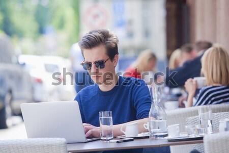 Młody człowiek laptop posiedzenia na zewnątrz działalności wody Zdjęcia stock © courtyardpix