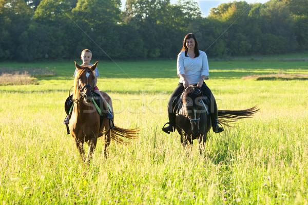 Horseback Riding Lessons - Woman Riding along a Boy on a Horse  Stock photo © courtyardpix