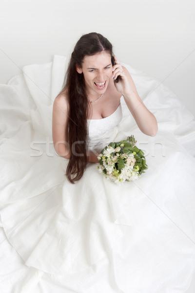 Mérges menyasszony mobiltelefon esküvői ruha virágcsokor kiabál Stock fotó © courtyardpix