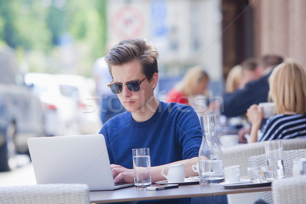 Young Man with Laptop Sitting in Outside Coffeehouse  Stock photo © courtyardpix