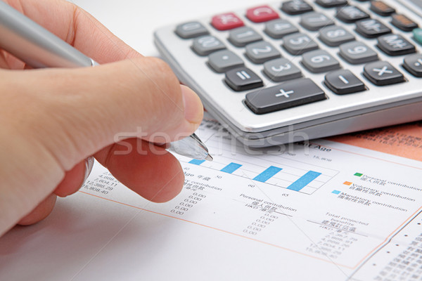 Businessman's hand showing diagram on financial report with pen. Stock photo © cozyta