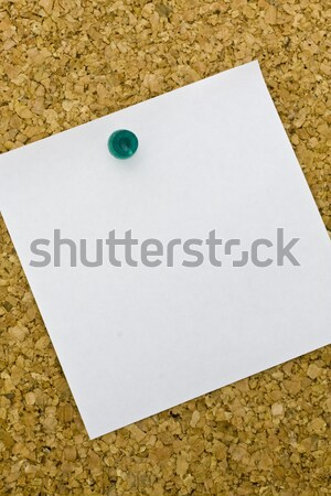 Yellow postit on a everyday corkboard.