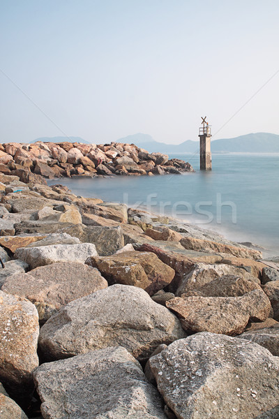Lighthouse on a Rocky Breakwall: A small lighthouse warns of a r Stock photo © cozyta