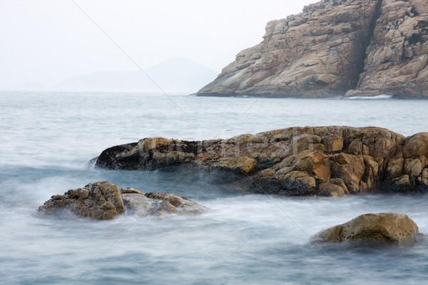 La exposición a largo rock costa puesta de sol paisaje fondo Foto stock © cozyta
