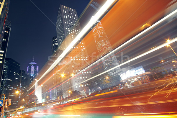Stock photo: traffic light trails in the street by modern building