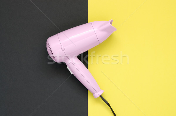 Pink hair dryer on black and yellow background Stock photo © CsDeli