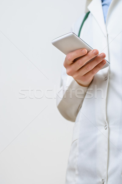 A female doctor texting on smartphone Stock photo © CsDeli