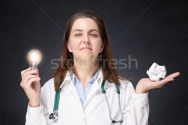 Doctor with glowing light bulb and crumpled paper Stock photo © CsDeli
