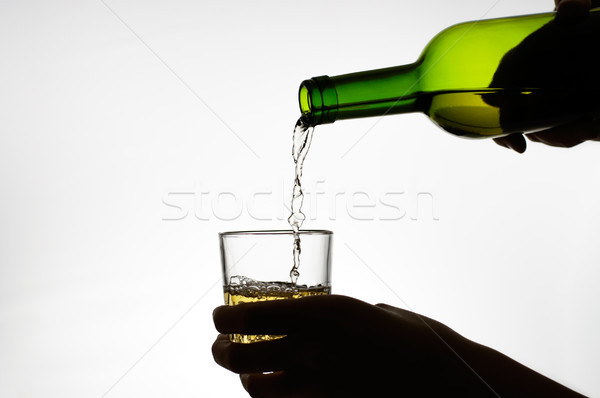 Female hand pouring wine into glass Stock photo © CsDeli