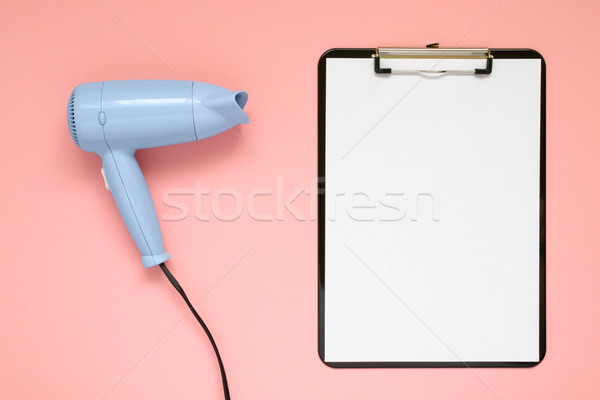 Stock photo: Blue hair dryer and clipboard on pink background