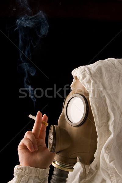 Persona maschera antigas fumare sigaretta buio sicurezza Foto d'archivio © ctacik