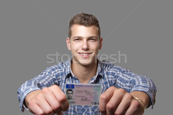Young man showing off his driver license Stock photo © Cursedsenses