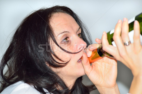 Drunk woman with red wine bottle Stock photo © cwzahner