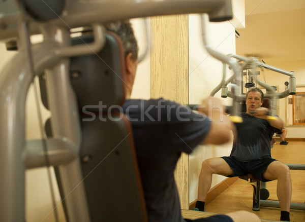 Mature man exercising on shoulder press machine Stock photo © d13