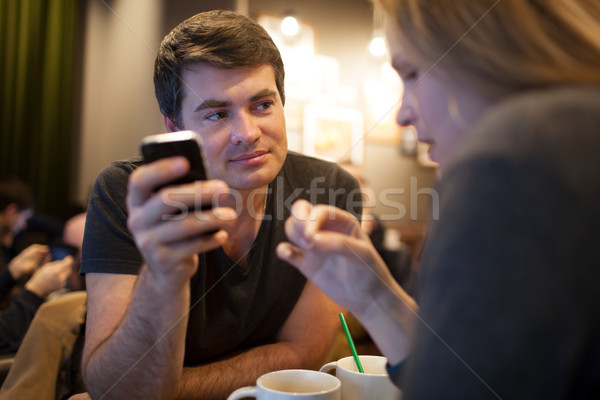 Man using mobile phone during meeting with girl in cafe Stock photo © d13