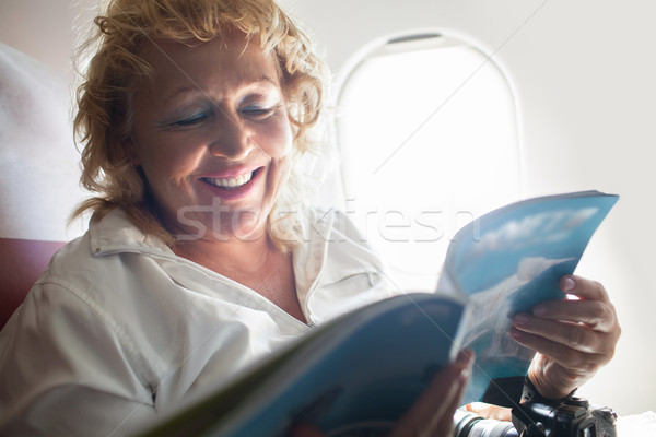 Mature Woman Reading Magazine on a Plane Stock photo © d13